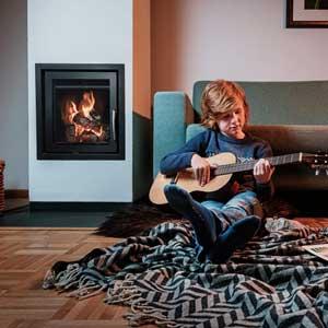 Junge spielt Gitarre vor HÖLZLI Kompaktspeicherofen