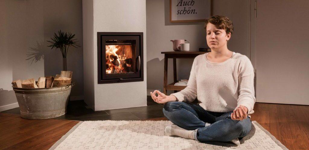 Frau meditiert vor dem Ofen
