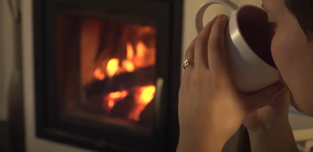 Frau trinkt Tee vor Ofenfeuer